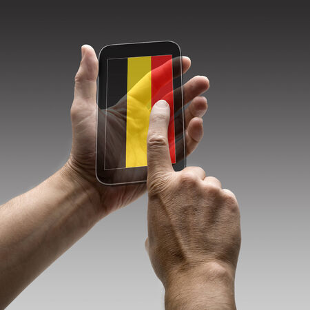 belgium flag: Holding Belgium flag screen smart phone. There is a route for hand and finger.  Stock Photo