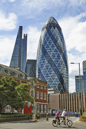 LONDON, UK- JUNE 06: The modern glass buildings of the Swiss Re Gherkin on June 06, 2014 in London, England. This tower is 180 meters tall and stands in the City of London Financial District.