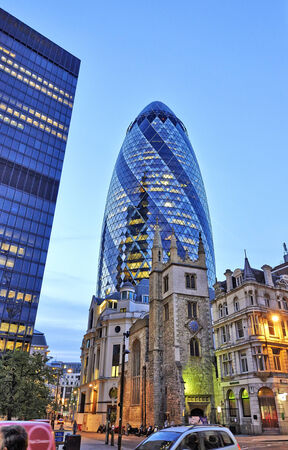 LONDON, UK- JUNE 06: The modern glass buildings of the Swiss Re Gherkin on Julne 06, 2014 in London, England. This tower is 180 meters tall and stands in the City of London Financial District.