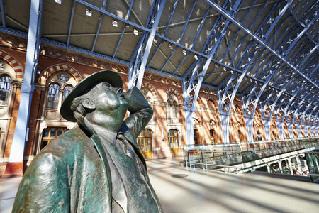 eurostar: LONDON - JUNE 8. Standing in the restored and redeveloped St Pancras International rail station is a statue of Sir John Betjeman who saved the building from demolition; June 8, 2014 in London, UK.