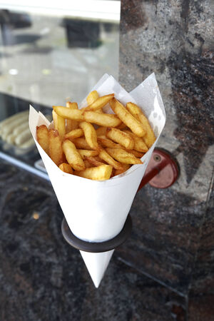 frites: Potatoes fries in a little white paper bag hanging at the wall from a belgian friterie
