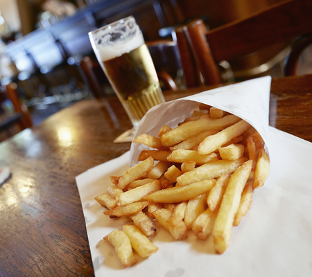 frites: Potatoes fries in a little white paper bag on wood table in brussels pub