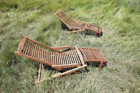 Two long wooden chairs in wild nature