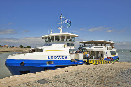 named: AIX ISLAND,CHARENTE MARITIME, FRANCE - JULY 11, 2014: Ferry named Ile daix II .A French gendarme supervises docks, this boat provides maritime link between Fouras and Aix island on July 11 in Aix island