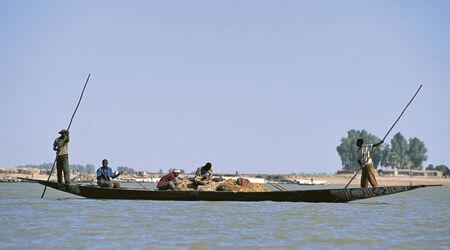 MOPTI, MALI - SEPTEMBER 17,2009: African fisherman pinnace navigating the river Niger in Mopti, most important commercial port of Mali, September 17, 2009 in Mopti, Mali