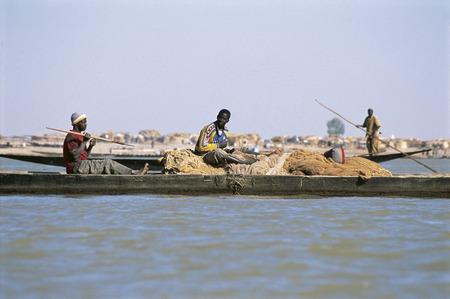 primitivism: MOPTI, MALI - SEPTEMBER 17,2009: African fisherman pinnace navigating the river Niger in Mopti, most important commercial port of Mali, September 17, 2009 in Mopti, Mali