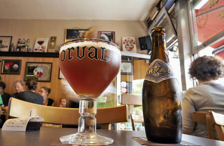 BRUSSELS, BELGIUM - JULY 27, 2014: Orval Trappist Belgian Ale bottle and glass on a table opposite in a typical Belgian tavern on 27 july,2014 in Brussels,Belgium. There are out of focus tourists on the tables in the background.