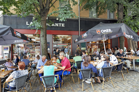 BRUSSELS, BELGIUM - JULY 27, 2014: People drink, eat and talk on the terrace of a cafe in the Old Market area of Brussels on July 27, 2014 in Brussels. a group of musicians play a few pieces of popular music