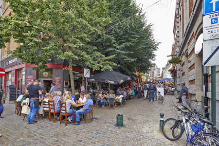 BRUSSELS, BELGIUM - JULY 27, 2014: People drink, eat and talk on the terrace of a cafe in the Old Market area of Brussels on July 27, 2014 in Brussels. The market takes place daily and is popular among local people and tourists.