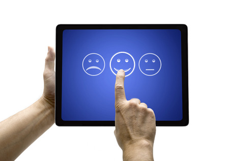 Hand touching screen with customer service evaluation form on a  tablet Фото со стока