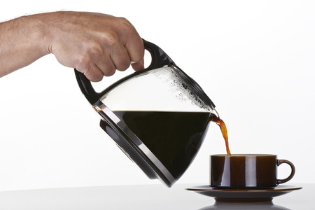 mans hand holding and pouring coffee into a brown cup Фото со стока