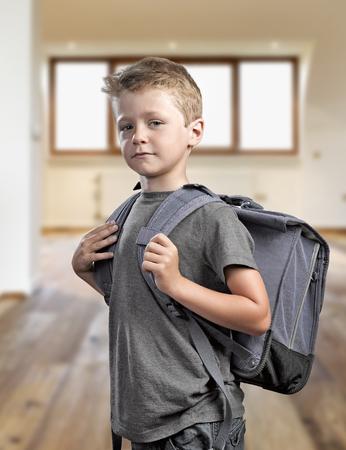 Junger Junge mit Rucksack isoliert auf weißem Hintergrund bereit, wieder in die Schule gehen Lizenzfreie Bilder