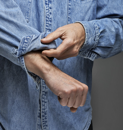 Man in denim shirt rolling up his sleeves Stock Photo