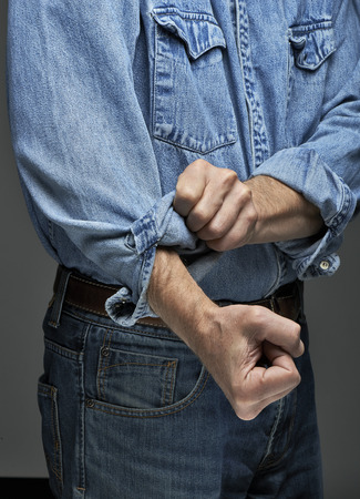 rolling up: Man in denim shirt rolling up his sleeves Stock Photo
