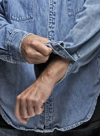 Man in denim shirt rolling up his sleeves 스톡 콘텐츠