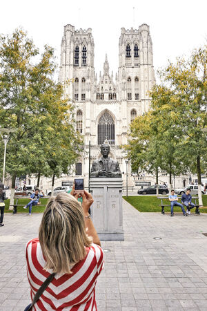 baudouin: BRUSSEL,BELGIUM - 07 SEPTEMBER 2014: Tourist holds up camera mobile from King Baudouin Statue in front of St. Michael and St. Gudula Cathedral in Brussels, Belgium, the 07 september 2014