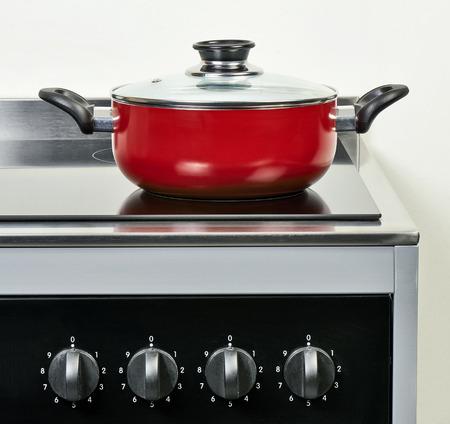 Red Keramiktopf mit Deckel auf Elektro-Kochfeld in der modernen und heimischen Küche Lizenzfreie Bilder