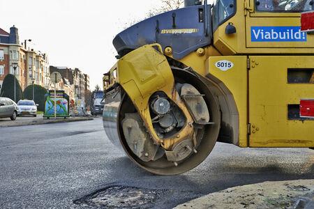 BRUSSEL, BELGIË - NOVEMBER 29, 2014: De zware verdichtingsrolpers bij de werken van de asfaltbestrating voor weg die op 29 November, 2014 in Brussel, België herstellen