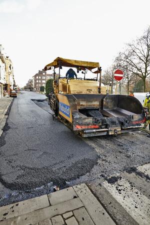 BRUSSEL, BELGIË - 29 november 2014: Een asfaltspreidmachine wordt gebruikt om asfaltlaag en stoomwals volgt op een stad straat vernieuwingsproject op 29 november 2014 in Brussel, België plaatst