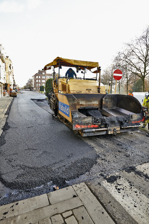 steam roller: BRUSSELS, BELGIUM - NOVEMBER 29, 2014:  An asphalt spreader is used to place layer of asphalt and steam roller follows on a city street renewal project  on November 29, 2014 in Brussels, Belgium