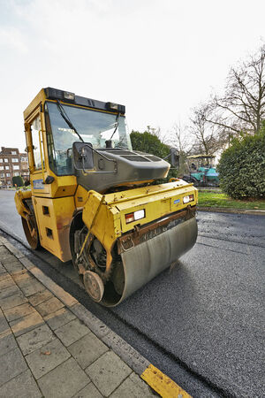 roller compactor: BRUSSELS, BELGIUM - NOVEMBER 29, 2014:  Heavy Vibration roller compactor at asphalt pavement works for road repairing on November 29, 2014 in Brussels, Belgium Editorial