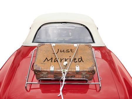 Just Married geschrieben auf einem Koffer auf dem Kofferraum eines roten Auto mit Clipping-Pfad gelegt