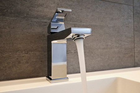 household fixture: Very high end faucet, sink, and counter in a luxury bathroom - with water split on