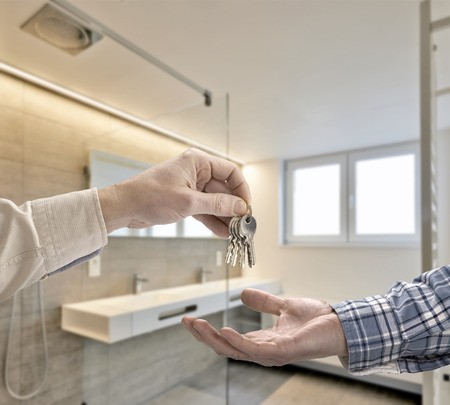 manor house: Realtor giving house key to buyer in Luxury Bathroom Estate Home Stock Photo