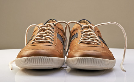untied: Brown Leather Shoe with white shoelaces open on a white table