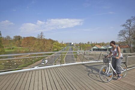 sovereign: BRUSSELS, BELGIUM - APRIL 16, 2015: Young woman with her bike on the bridge at the Tervueren avenue in Brussels, Belgium. This metal pedestrian bridge overcomes the Avenue de Tervuren, the Sovereign boulevard and the Museum of Urban Transport of Brussels.