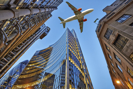 Een vliegtuig vliegt laag over drie verschillende soorten architectuur buitenkant handel met kantoorgebouwen. Avond uitzicht onderaan wolkenkrabbers.