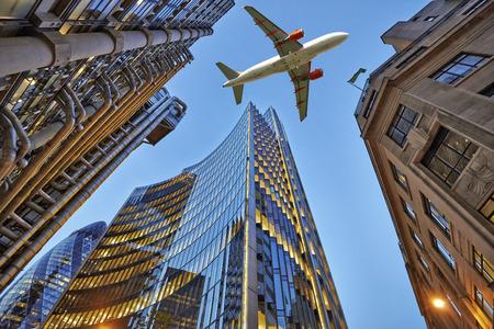 Ein Düsenflugzeug niedrig fliegen über drei verschiedene Arten von Architektur Außenhandel mit Bürogebäuden. Abendansicht unten Wolkenkratzer. Lizenzfreie Bilder