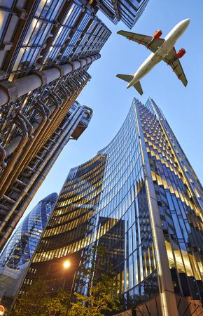 Ein Düsenflugzeug niedrig fliegen über drei verschiedene Arten von Architektur Außenhandel mit Bürogebäuden. Abendansicht unten Skyscrape Lizenzfreie Bilder