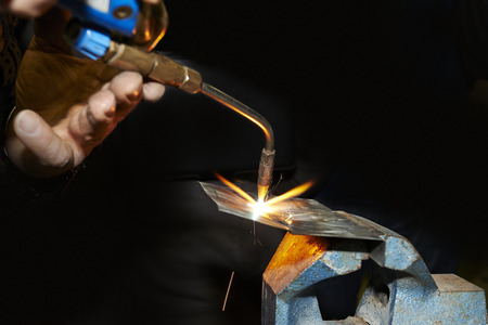 machinist: Welder working his trade, some sparks flying from the torch