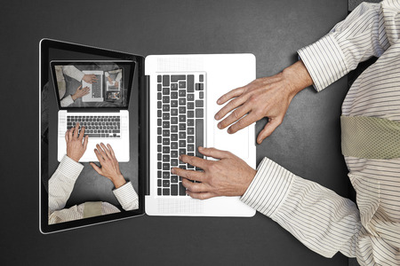 handcarves: Businessman wearing a white shirt and green tie working on his laptop. Droste effect on screen