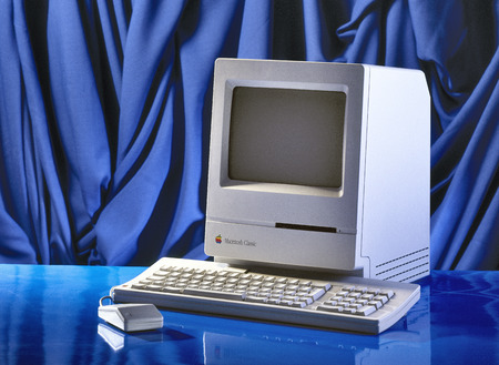 BRUSSEL,BELGIUM - CIRCA YEAR: Old Fashioned Computer and Mouse on Office Desk. Model Apple Macintosh Classic from 1990 Editorial