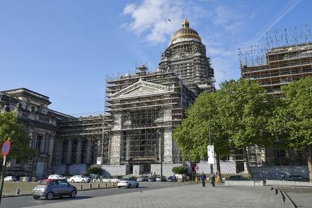 justicia: Bruselas, B�lgica - 27 de mayo, 2015: Dos policemans caminar delante de uno de los edificios m�s grandes construidas en el siglo 19. El Tribunal de leyes o Palacio de Justicia en reconstrucci�n. El edificio de la Corte m�s importante construido entre 1866 y 1883 por una
