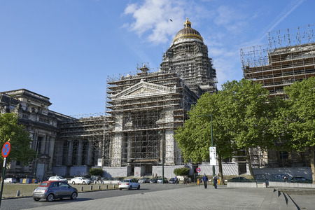 justice: BRUSSELS, BELGIUM - MAY 27, 2015: Two policemans walk in Front of one of the largest buildings constructed in the 19th century. The Court of Laws or Palace of Justice under reconstruction. The most important Court building built between 1866 and 1883 by a