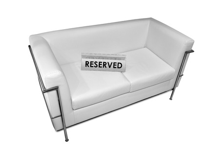 reserved sign: Reserved sign on white leather sofa isolated on white background with clipping path Stock Photo