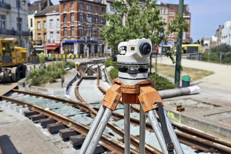 land surveying: BRUSSELS, BELGIUM -16 JULY 2015: Land Surveying on construction site and some workers repair and replace rail trams in Brussels at Verboekhoven square in Schaerbeek. Editorial