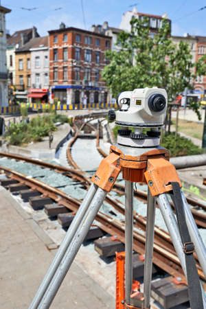 tacheometer: BRUSSELS, BELGIUM -16 JULY 2015: Land Surveying on construction site and some workers repair and replace rail trams in Brussels at Verboekhoven square in Schaerbeek. Editorial