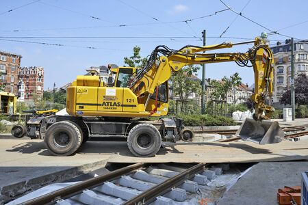 BRUSSELS, BELGIUM -16 JULY 2015: bulldozer on construction site and some workers repair and replace rail trams in Brussels at Verboekhoven square in Schaerbeek.