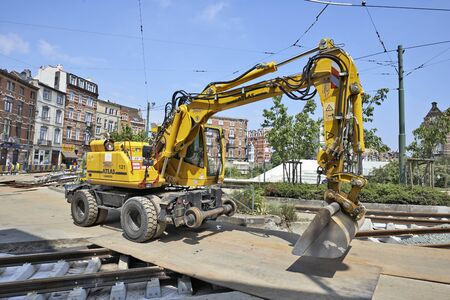 ours: BRUSSELS, BELGIUM -16 JULY 2015: bulldozer on construction site and some workers repair and replace rail trams in Brussels at Verboekhoven square in Schaerbeek.