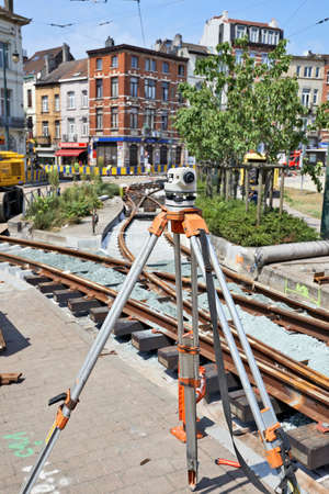 ours: BRUSSELS, BELGIUM -16 JULY 2015: Land Surveying on construction site and some workers repair and replace rail trams in Brussels at Verboekhoven square in Schaerbeek. Editorial