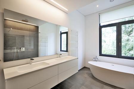 Banheira em corian, torneira e chuveiro na casa de banho com janelas em direção jardim