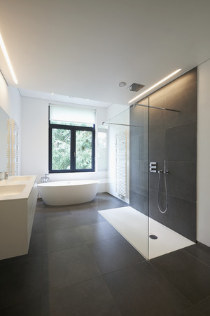 bathroom tile: Bathtub in corian, Faucet and shower in tiled bathroom with windows towards garden