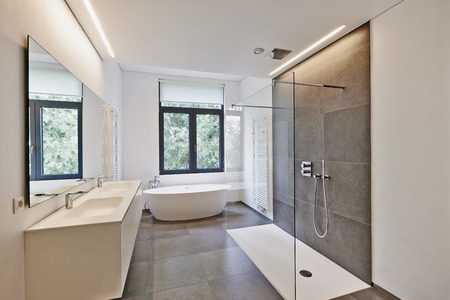 shower: Bathtub in corian, Faucet and shower in tiled bathroom with windows towards garden