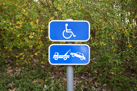 physical impairment: A handicap parking sign and car removal sign on green background