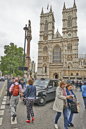 victorian architecture: LONDON, UK - JUNE 07, 2014:  Some tourists and visitors wander outside the entrance to Westminster Abbey Editorial