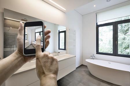 case moderne: dispositivo mobile con mani dell'uomo di scattare una foto in bagno piastrellato con finestre verso giardino Archivio Fotografico